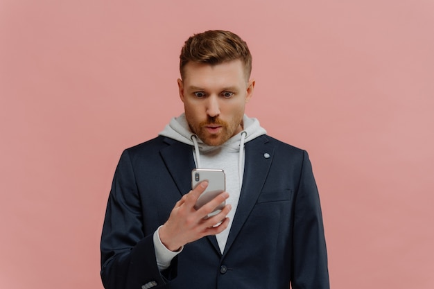 Das kann nicht wahr sein. beeindruckter gutaussehender rothaariger mit bart in jacke über hoodie, der die lippen in wow faltet, unglaubliche nachrichten in seinem handy liest, während er isoliert über rosa wand steht.