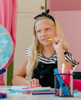 Das kaukasische blonde schulmädchen träumt oder denkt während des studiums. bildungskonzept