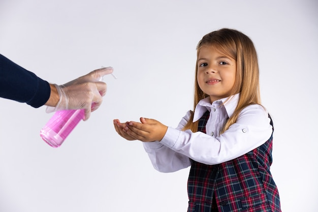 Das kaukasische grundschülerin in schuluniform desinfiziert ihre hände, bevor sie das auf der weißen wand isolierte klassenzimmer betritt.