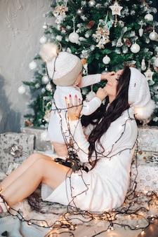 Das kaukasische kleine baby spielt und hat viel spaß mit seiner mutter in der nähe des weihnachtsbaumes