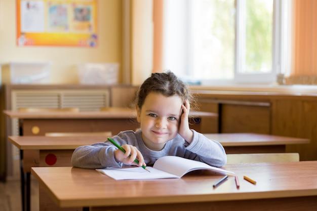 Das kaukasische kleine lächelnde mädchen, das am schreibtisch im klassenzimmer sitzt und fängt an, in ein reines notizbuch zu zeichnen