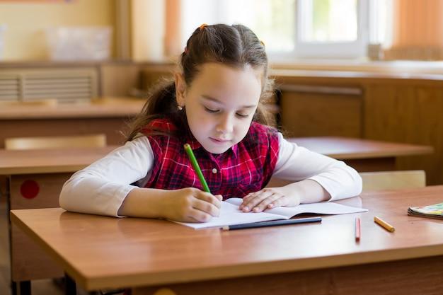 Das kaukasische mädchen, das am schreibtisch im klassenzimmer sitzt und fängt an, in ein reines notizbuch sorgfältig zu zeichnen. prüfungsvorbereitung