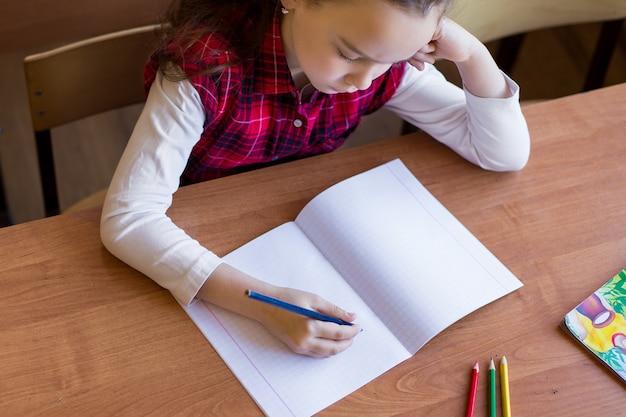 Das kaukasische mädchen, das am schreibtisch im klassenzimmer sitzt und fängt an, in ein reines notizbuch zu zeichnen.