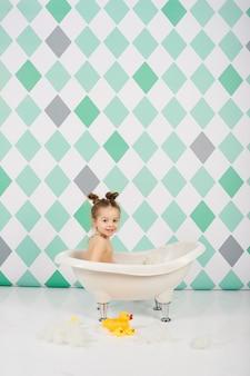 Das kaukasische mädchen des lustigen babys, das mit wasser badet und spielt, spielt nahe blumen