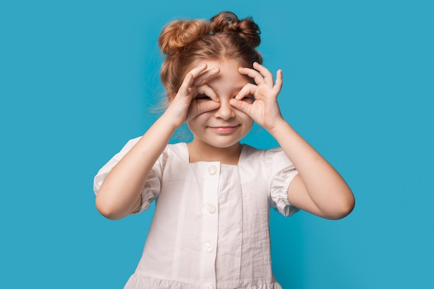 Das kaukasische mädchen gestikuliert ein fernglas mit den fingern, die an der kamera auf einer blauen studiowand lächeln, die ein kleid trägt