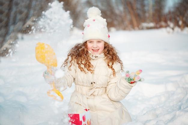 Das kind, das mit einem schnee auf einem winter spielt, gehen in den park.