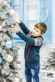 Das kind, das verzierungen auf den weihnachtsbaum setzt