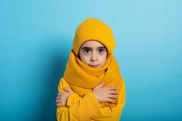 Das kind deckt sich ab, um sich nicht zu erkälten. cyan hintergrund