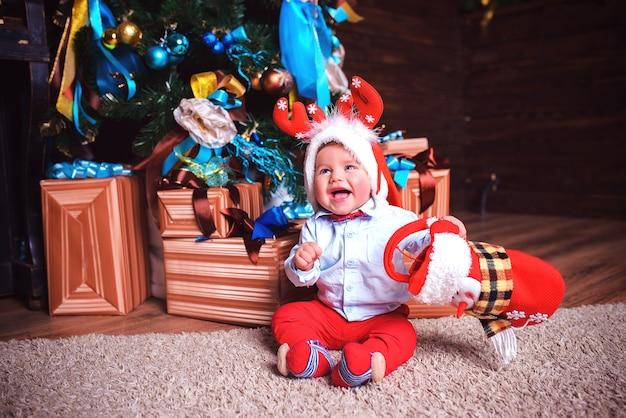Das kind freut sich an einem festlichen tag in der nähe des weihnachtsbaumes