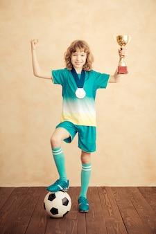 Das kind gibt vor, ein fußballspieler zu sein. erfolgs- und gewinnerkonzept