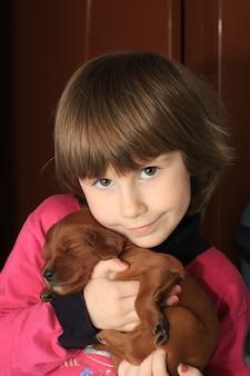 Das kind hält an den händen eines kleinen welpen