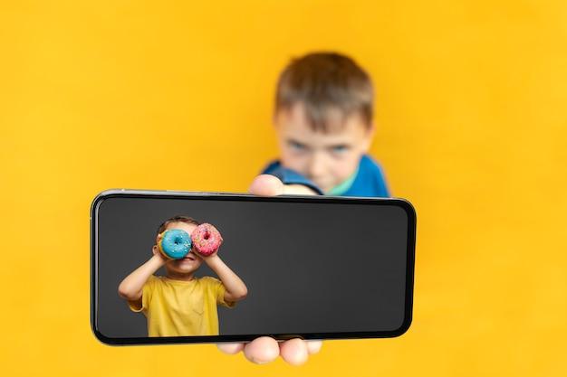 Das kind hält das telefon für werbung auf gelbem grund in der hand. farbe