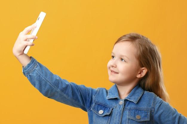 Das kind hält das telefon in der hand und macht ein selfie