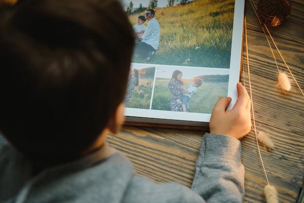 Das kind hält ein familienfotoalbum auf einem holztisch