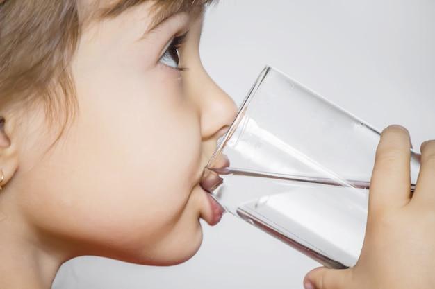 Das kind hält ein glas wasser in den händen. selektiver fokus.