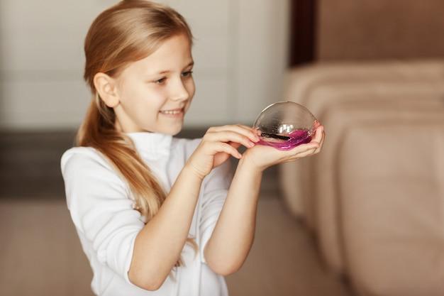 Das kind hält ein spielzeug, das schleim genannt wird, das kind hat spaß und experimentiert.