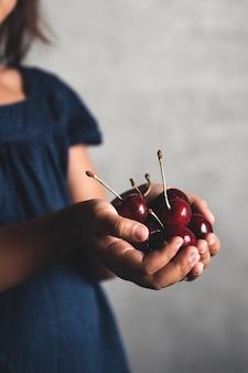 Das kind hält eine köstliche kirsche in den händen. schöne saftige beere. eine handvoll kirschen. vegan, öko, landwirtschaftliche produkte, bio-lebensmittel