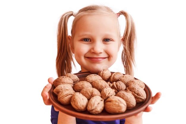 Das kind hält einen teller mit nüssen und lächelt