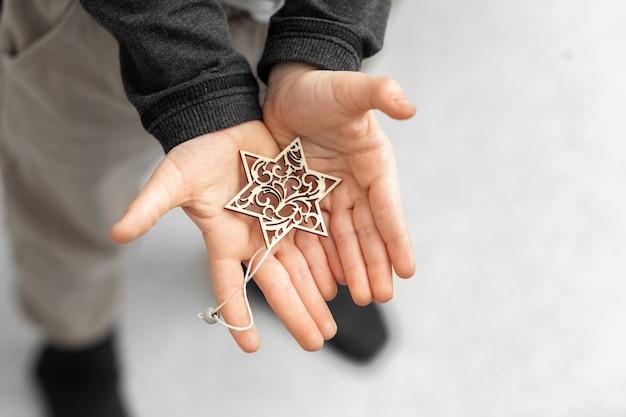 Das kind hält in seinen händen eine dekorative schneeflocke einen stern dekoration für den weihnachtsbaum