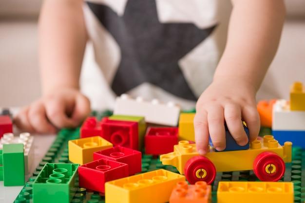 Das kind hat spaß beim spielen mit bunten plastiksteinen am tisch