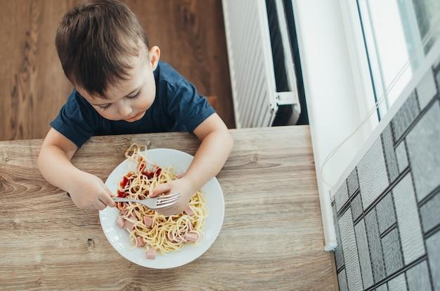 Das kind in der küche am tisch isst makkaroni und interessante aussicht von oben