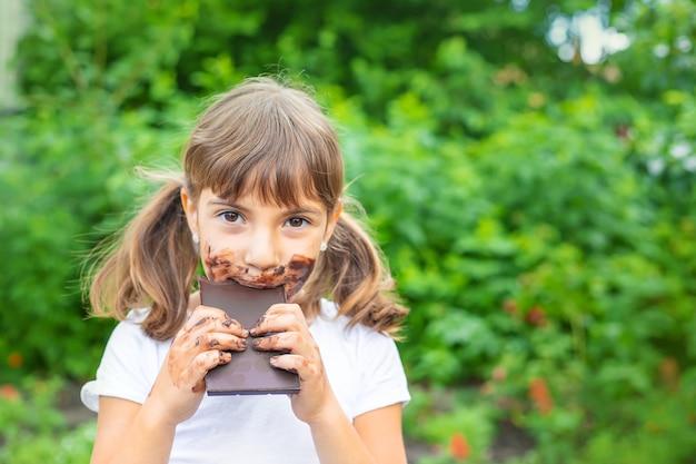 Das kind isst eine tafel schokolade.