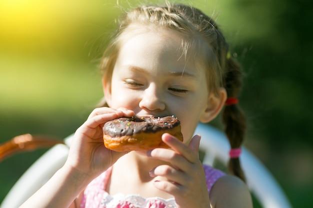 Das kind isst einen süßen donut.