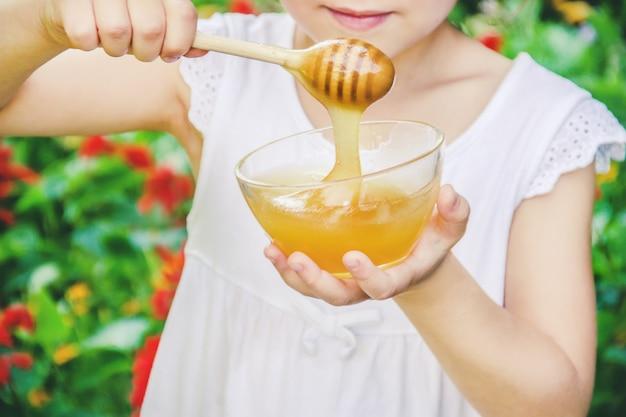 Das kind isst honig. selektiver fokus natur.