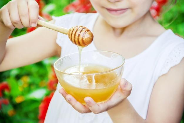 Das kind isst honig. selektiver fokus naturnahrung
