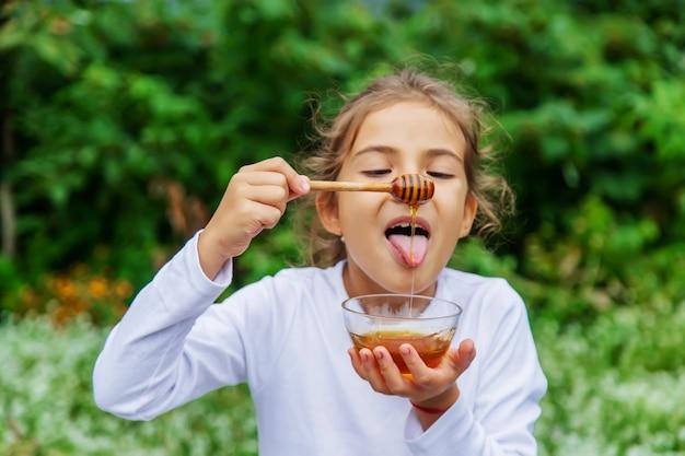 Das kind isst honig und äpfel. selektiver fokus.essen