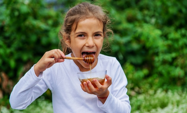 Das kind isst honig und äpfel. selektiver fokus.