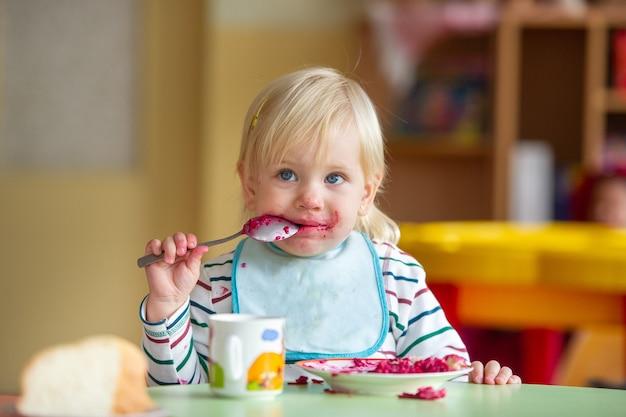 Das kind isst im kindergarten oder zu hause gesundes essen und wird schmutzig