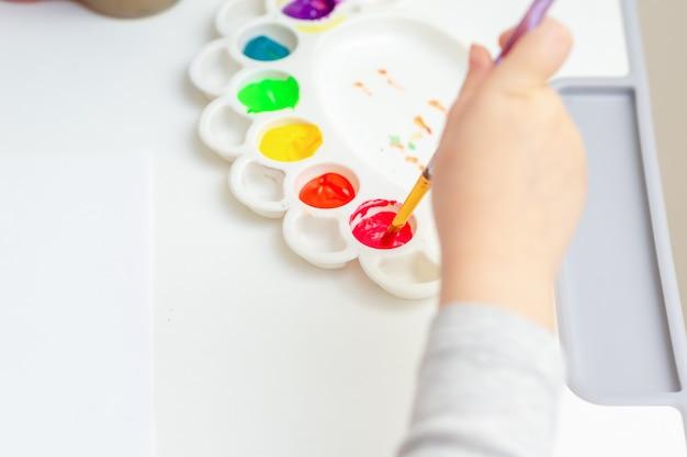 Das kind ist bereit, mit aquarellen zu malen.