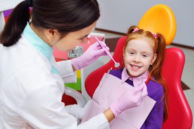 Das kind ist ein kleines rothaariges lächelndes mädchen, das auf einem zahnarztstuhl sitzt. kinderzahnheilkunde, milchzähne