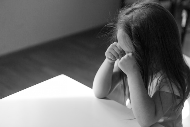 Das kind ist gelangweilt, trauriges gesicht. das mädchen weint. das konzept von kindheit, kindertag, kindergarten-copyspace, schlechter laune, hausarrest, ungehorsam, elternschaft, aufregung, emotionen
