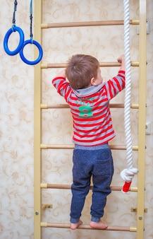 Das kind klettert die treppe hoch. gymnastik kindersport schwedische wand.