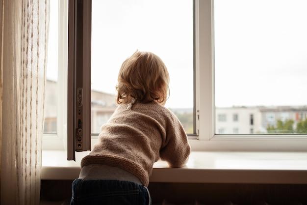 Das kind klettert zum fenster, das mädchen auf der fensterbank ruht im netz