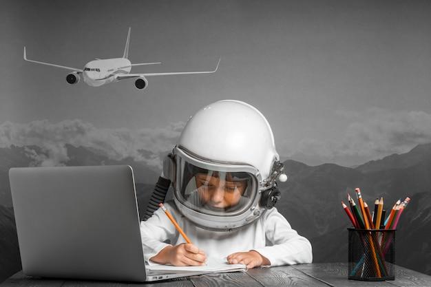 Das kind lernt aus der ferne in der schule und trägt einen pilotenhelm. zurück zur schule
