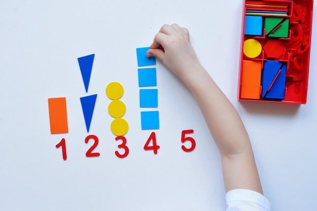 Das kind lernt zahlenlinien und geometrische formen. der vorschulkind arbeitet mit montessori-material.