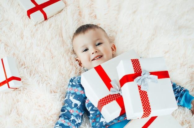 Das kind liegt auf der flauschigen flauschigen decke, neben ihm ein haufen geschenke, das kind freut sich sehr
