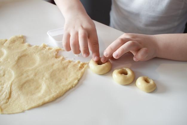Das kind macht plätzchenformen auf einer weißen tabelle. zubereitung von hausgemachten dessert. nahansicht