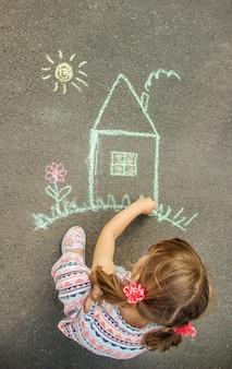 Das kind malt das haus mit kreide auf den asphalt. tiefenschärfe.