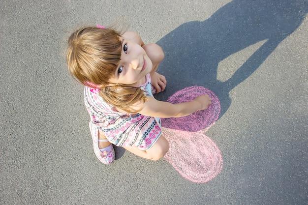 Das kind malt kreide auf das asphaltherz. selektiver fokus