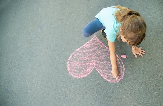 Das kind malt kreide auf das asphaltherz. tiefenschärfe.