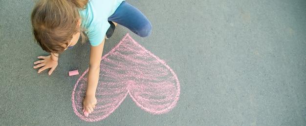 Das kind malt kreide auf das asphaltherz.