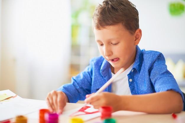 Das kind malt mit einem pinsel aquarell auf papier den buchstaben a