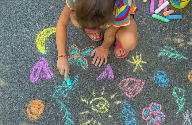 Das kind malt mit kreide auf den asphalt