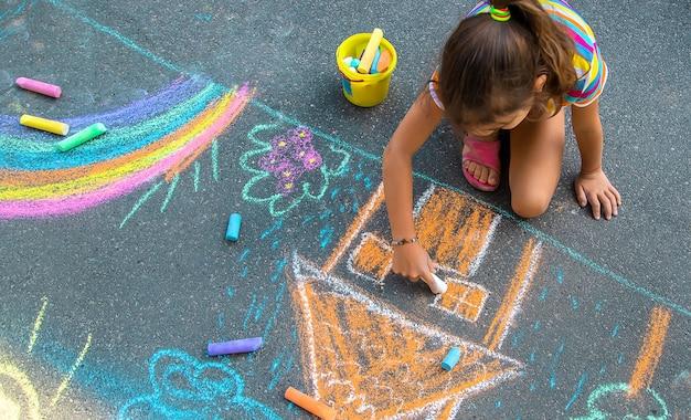 Das kind malt mit kreide ein haus und einen regenbogen auf den asphalt