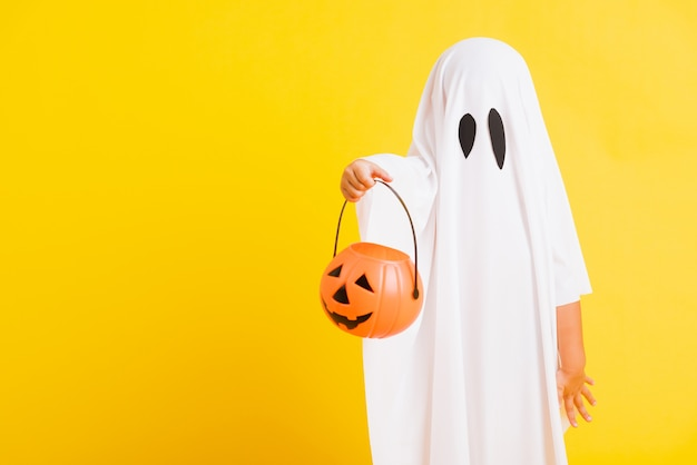 Das kind mit dem weiß gekleideten kostüm halloween-geist beängstigend hält er orange kürbisgeist zur hand