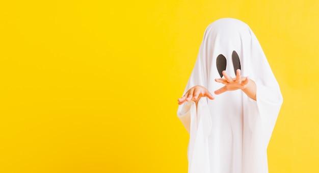 Das kind mit dem weiß gekleideten kostüm halloween-geist beängstigend